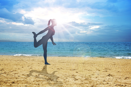 physical training: Silhouette illustration of a woman stretching her leg on the beach Stock Photo