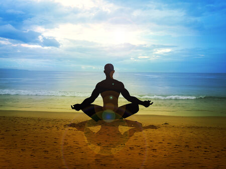 Silhouette of a male figure meditating on the beach photo