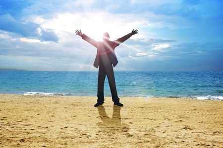 relieved: A man standing on beach with open arms with sunset as the background Stock Photo
