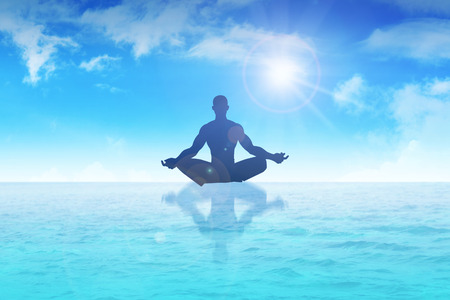 Silhouette of a man figure meditating on water photo