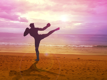 self training: Silhouette illustration of a kick boxer training at the beach