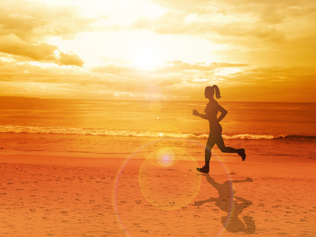 nature scenery: Woman jogging alone at beautiful sunset in the beach, summer sport and freedom concept