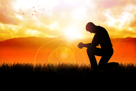 inner peace: Silhouette illustration of a man praying outside at beautiful landscape Stock Photo