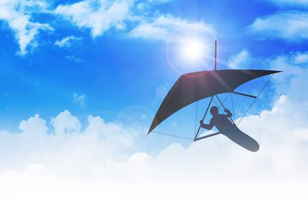hang glider: Silhouette of hang glider flying among clouds