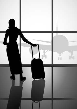 airport window: Silhouette of a woman with luggage looking at the airport window