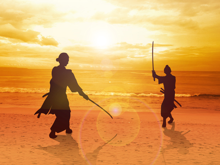 facing each other: Two Samurai in duel stance facing each other on the beach Stock Photo
