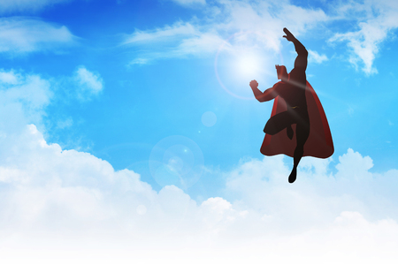 tough man: Silhouette of a superhero figure flying on clouds