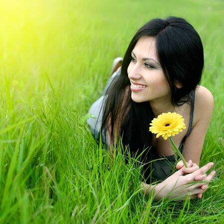 beautiful young woman relaxing in the grass photo