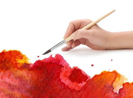 hand with brush and watercolor paint photo