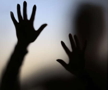 scary hand: diffused silhouette through frosted glass Stock Photo