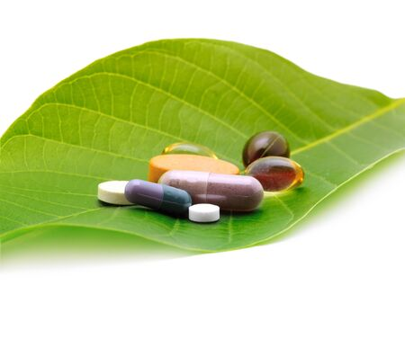 vitamins, tablets and pills on green leaf photo