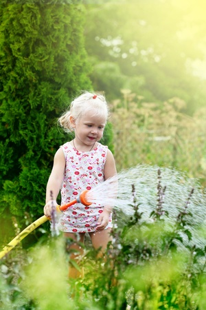 moisten: Little girl watering the grass in the garden Stock Photo