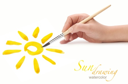 hand with brush drawing sun, isolated