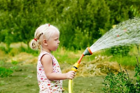 Meisje besproeien van het gras in de tuin Stockfoto