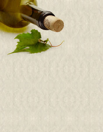 textured background with wine bottle and grape leaf photo