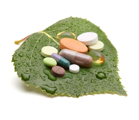 vitamins, tablets and pills on green leaf Stock Photo