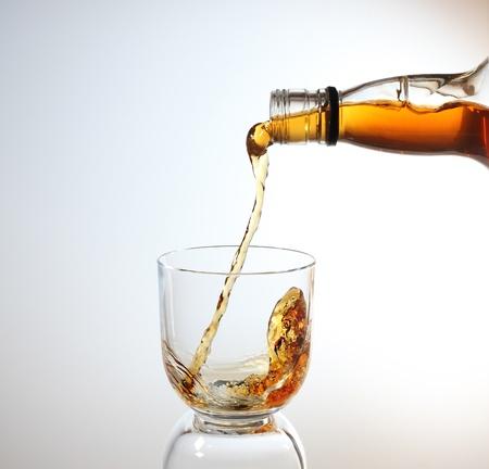 botella de whisky: whisky que se vierte en un vaso