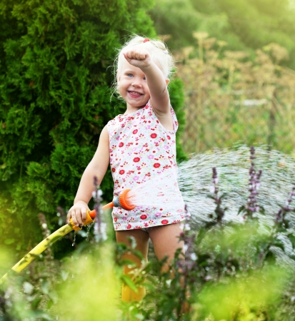 drench: Little girl watering the grass in the garden Stock Photo