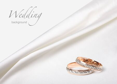 wedding rings on white silk background photo