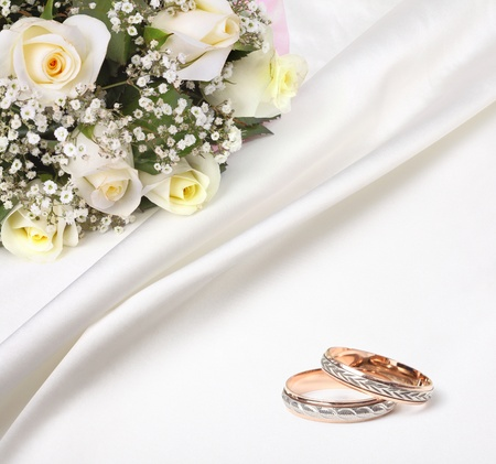 betrothal: wedding rings and roses bouquet