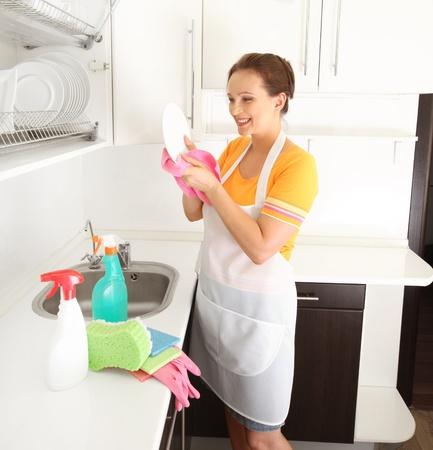 lavar trastes: mujer lavando la placa en la cocina