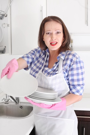 scouring: angry woman washing plate in kitchen Stock Photo