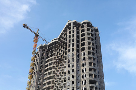 concrete construction: Crane and building house under blue sky