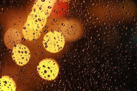 night views: Water drops on window glass. Night city views de-focus.