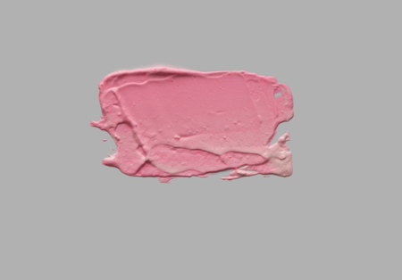 Pink brush stroke on uniform gray empty wall. Abstract background. Isolated on gray.