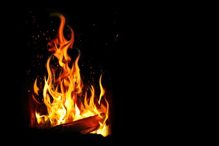 Burning log and fire on black background. Banco de Imagens