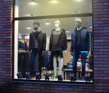 Night shopwindow with man and woman dressed mannequins