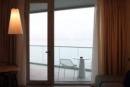 Living room with glass door to balcony. Sea view. Stock Photo