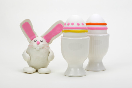 Plasticine rabbit with easter eggs on white background. Stock Photo - 120872477