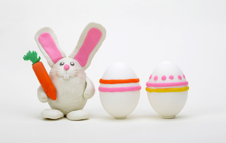 Plasticine rabbit with easter eggs on gray background. Stock Photo - 120872479
