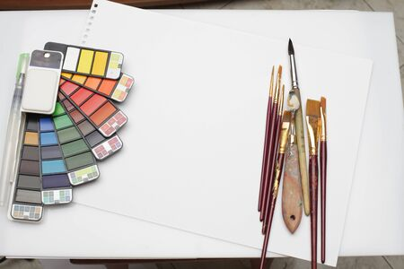 Watercolor paint rainbow palette with brush on white texture paper. Flat lay. Top view.. 版權商用圖片