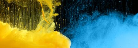 Acrylic blue and yellow colors in water. Ink blot. Abstract black background. Horizontal long banner. Фото со стока
