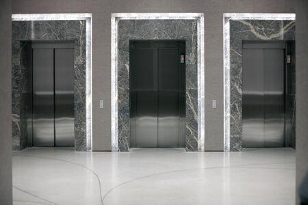 Three elevator entrances in an empty interior.