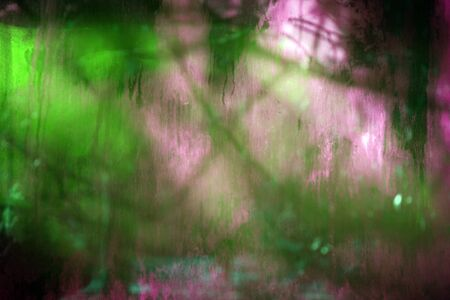 Old dirty dusty window glass with mystical reflection. Soft focus.  Abstract background with scratches. Green and magenta color.