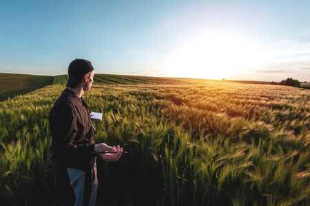 Young agronomist in cap takes notes in a notebook on a green agricultural field during sunset