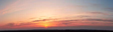 Panorama of red sunset. The yellow sun disappeared behind striped clouds