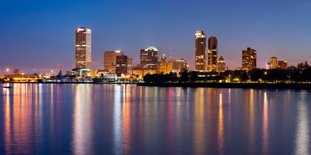 City of Milwaukee skyline. Image of Milwaukee skyline at twilight with city reflection in lake Michigan.