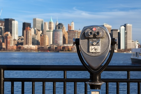 operated: Coin operated binoculars. Coin operated binoculars with New York skyline in the background.