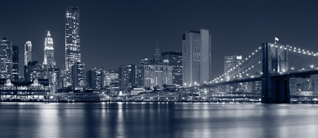 new york at night: Manhattan, New York City. Image of Brooklyn Bridge with Manhattan skyline in the background.