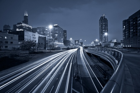 Nighttime highway traffic. Toned image of multi lane highway in Chicago downtown.