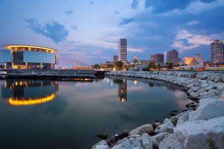Milwaukee: City of Milwaukee skyline. Image of Milwaukee skyline at twilight with city reflection in lake Michigan and harbor pier.