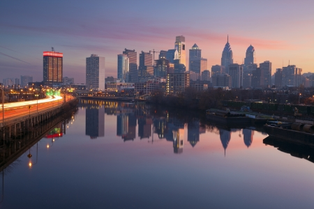 philadelphia: City of Philadelphia. Image of Philadelphia skyline in a morning mist, Schuylkill River and busy highway leading in to the city during sunrise.