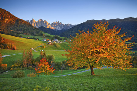 Beautiful St. Magdalena village in a gorgeous Funes Autumn in Alps. Valley located in Italian Alps during autumn sunset.