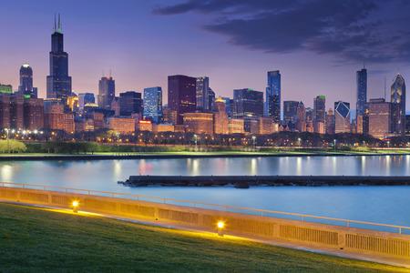 시카고의 스카이 라인. 미시간 호수의 도시의 불빛의 반사와 밤에 시카고 스카이 라인의 이미지입니다.