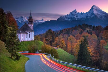 Autumn in Alps. Image of  the european Alps with Maria Gern Church during beautiful autumn sunset.