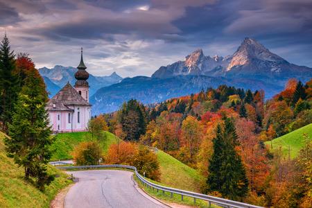 Autumn in Alps. Image of the Bavarian Alps with Maria Gern Church and Watzmann mountain during beautiful autumn sunrise. Stock Photo